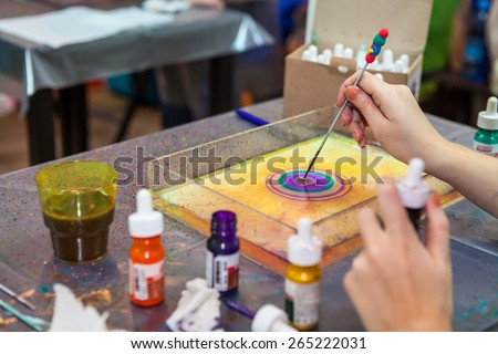 Man drawing with stick stained inks on water surface - stock photo