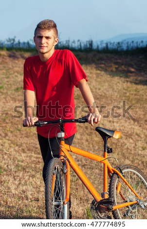 Man dresed red in sports clothing posing with orange bike at meadow
