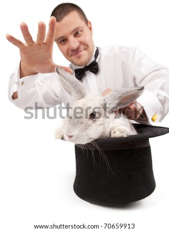 Man dressed as a magician conjuring with a rabbit in a top hat isolated over a white background - stock photo