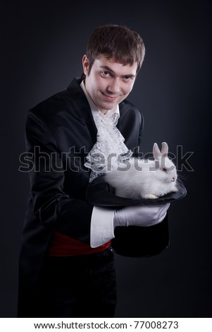 man dressed as a magician pulling a rabbit from his hat - stock photo