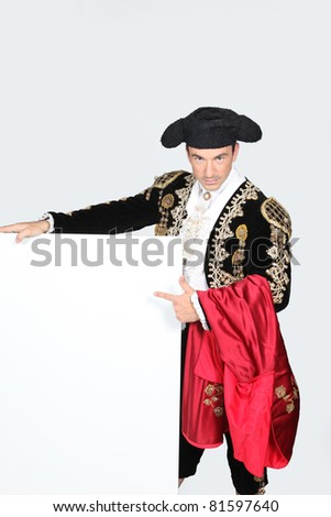 Man dressed as matador stood with blank message board - stock photo