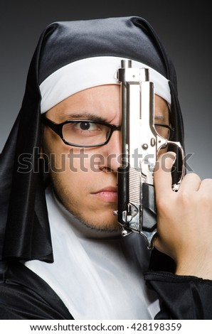 Man dressed as nun with handgun - stock photo