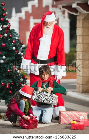 Man dressed as Santa Claus looking at children opening Christmas presents in courtyard - stock photo