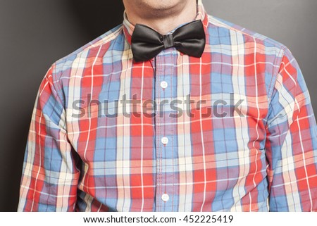 Man Dressed Checkered Shirt With Black Bow Tie On Gray - stock photo