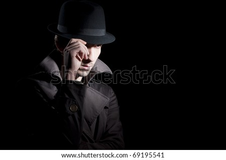 man dressed in a trench with a hat on his head isolated on black - stock photo