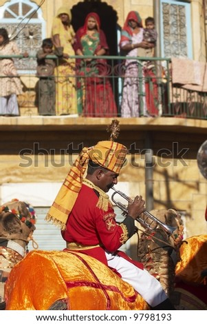 Man dressed in brightly colored uniform and playing a trumpet rides a camel through the streets of Jaisalmer watched by people on a balcony. Desert Festival, Jaisalmer, Rajasthan, India - stock photo
