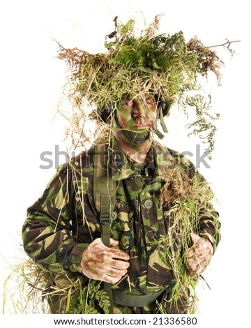 Man dressed in British Army camouflage enhanced with grasses and ferns