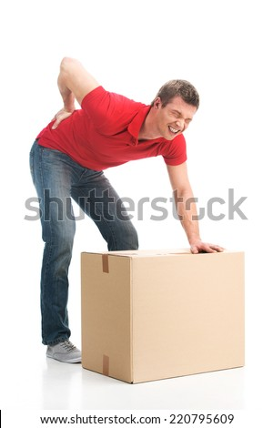 man dressed in casual clothing hurt his back lifting large box. young man suffering from back pain isolated on white background - stock photo