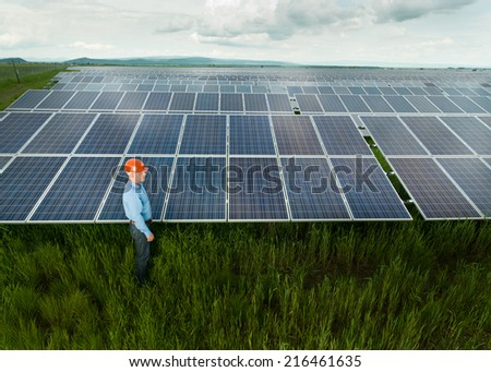 man dressed in engineer clothes and equipment standing near solar panels, outdoors, with clouded sky - stock photo