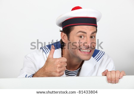 Man dressed in sailor costume with message board - stock photo