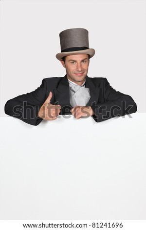 Man dressed in wedding attire with blank message board - stock photo