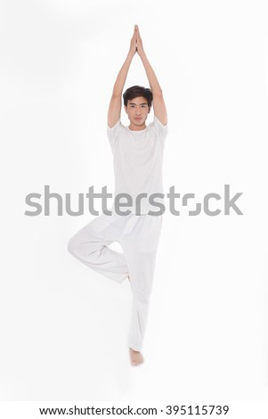 man dressed in white practicing yoga - stock photo