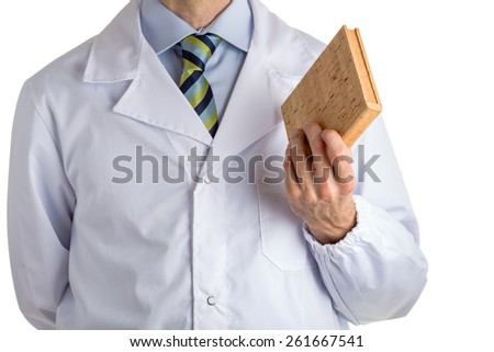 Man dressed with medical white coat and regimental tie is showing a blank cork book