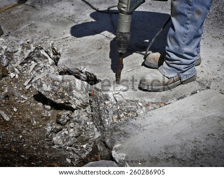 Man drilling cement concrete road - stock photo