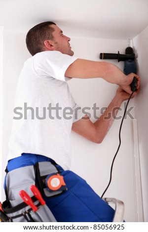 Man drilling hole in ceiling - stock photo