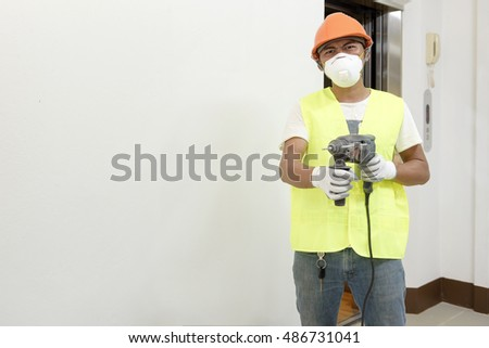 Man drilling the wall with Impact drill