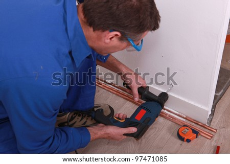 Man drilling through wall - stock photo