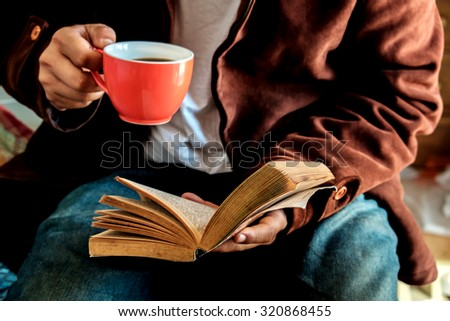 Man drinking a coffee and reading a book. - stock photo
