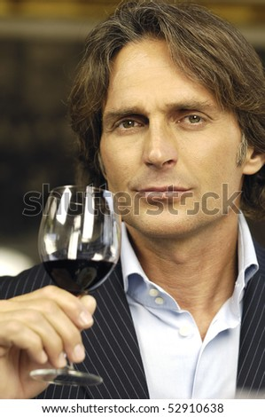 man drinking a glass of red wine - stock photo
