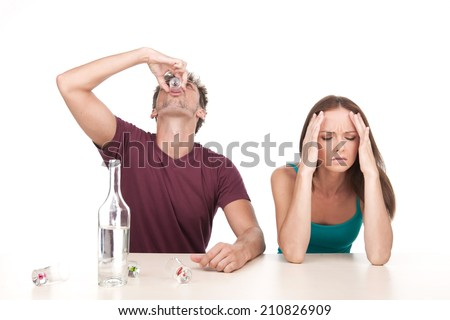 Man drinking alcohol and woman sitting upset at table. Photo of woman with alcoholic husband on white background - stock photo