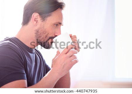 Man drinking and looking away - stock photo
