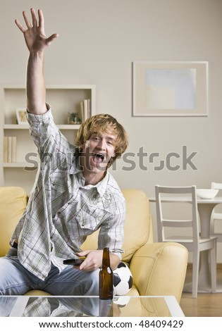 Man drinking beer and watching sports - stock photo