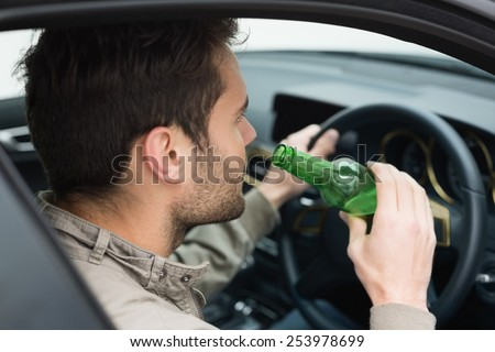 Man drinking beer while driving in his car - stock photo