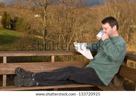 Man drinking coffee and reading the newspaper - stock photo