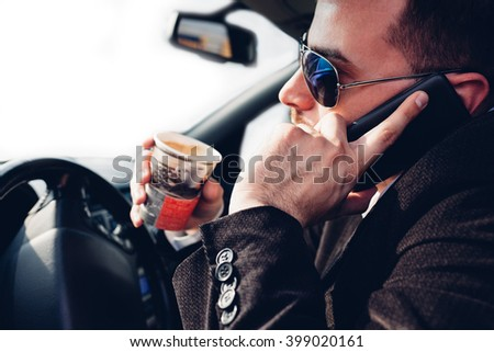Man drinking coffee and using mobile phone while driving car - stock photo