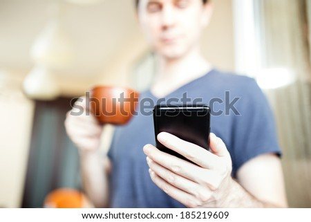Man drinking coffee and using mobile smartphone - stock photo