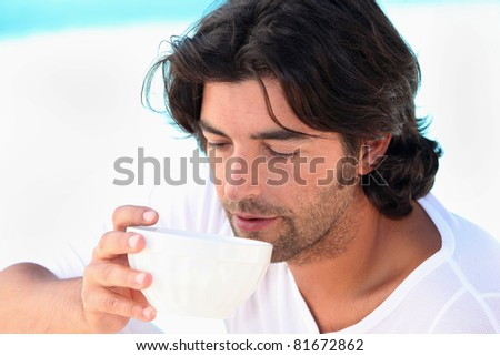 Man drinking coffee by swimming pool - stock photo