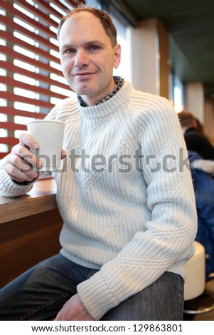 Man drinking coffee in a fast food restaurant