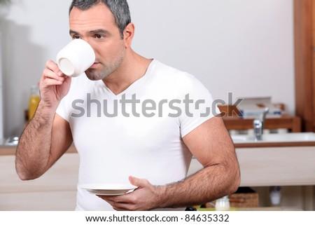 Man drinking coffee in kitchen - stock photo