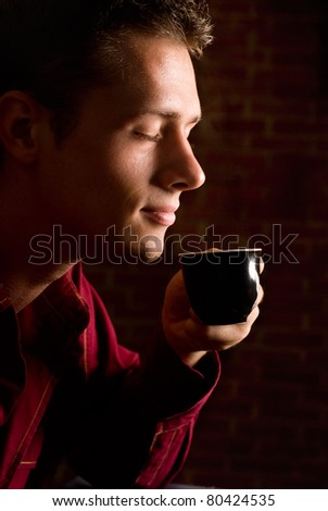 man drinking coffee on  a brick background