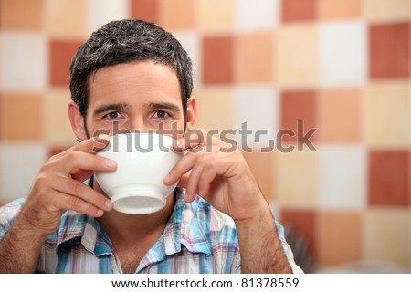 Man drinking from a white bowl in a tiled kitchen - stock photo