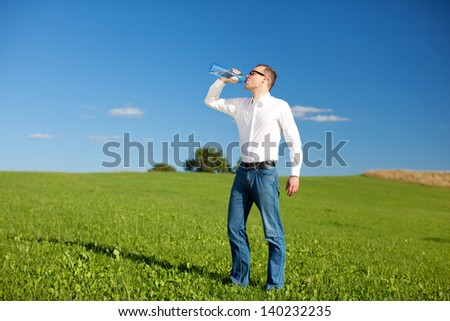 Man drinking mineral water quenching his thirst as he stands in a beautiful green field on a sunny day - stock photo