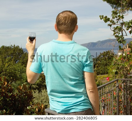 Man drinking red wine from glass, he is on vacation. The man against the sky, the sea, mountains and green plants. Man tasting wine. View from the back. It stands - rear view. South. Europe. - stock photo