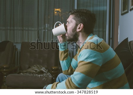 Man drinking tea at his room while watching TV - stock photo