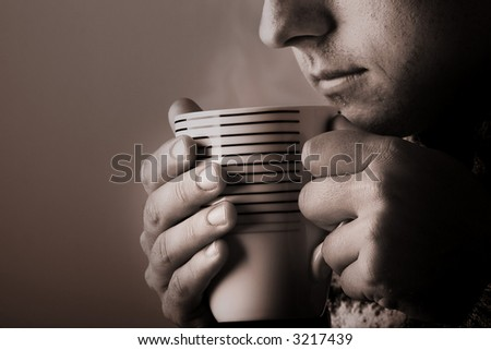 Man drinking warm beverage. Low key image. Sepia toned. Steam from cup - stock photo