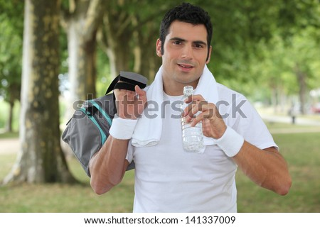 Man drinking water after a run in the park - stock photo