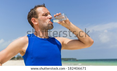 Man drinking water after running at beach. Thirsty sport runner resting taking a break with water bottle drink outside after training - stock photo
