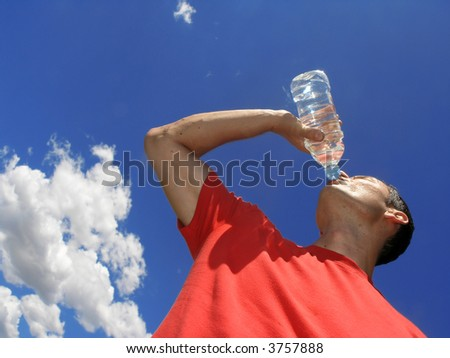 Man drinking water against blue sky - stock photo