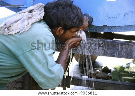 man drinking water from tank, south india - stock photo