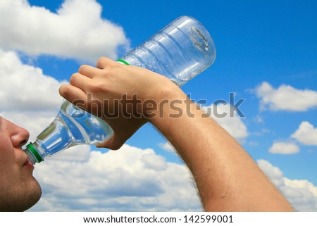 Man drinking water out of polyethylene plastic bottle in front of a blue sky