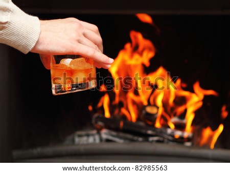 Man drinking whiskey by the fireplace - stock photo