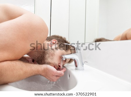 Man drinks tap water from the bathroom sink