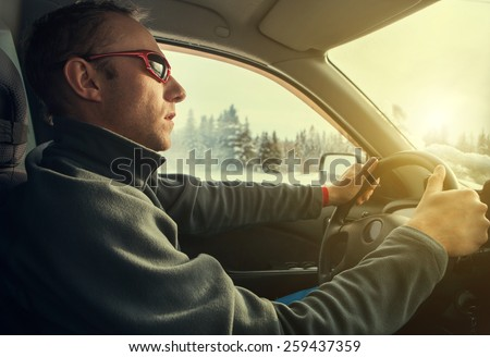 Man drive his car on the winter road - stock photo