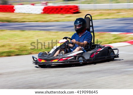 man drive karting car on outdoor track - stock photo