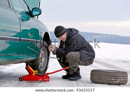 man driver having trouble at road changing wheel, repairing car, unscrewing bolts - stock photo