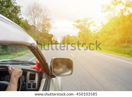 Man driver holding steering wheel right on rural road shady, sunlight effect